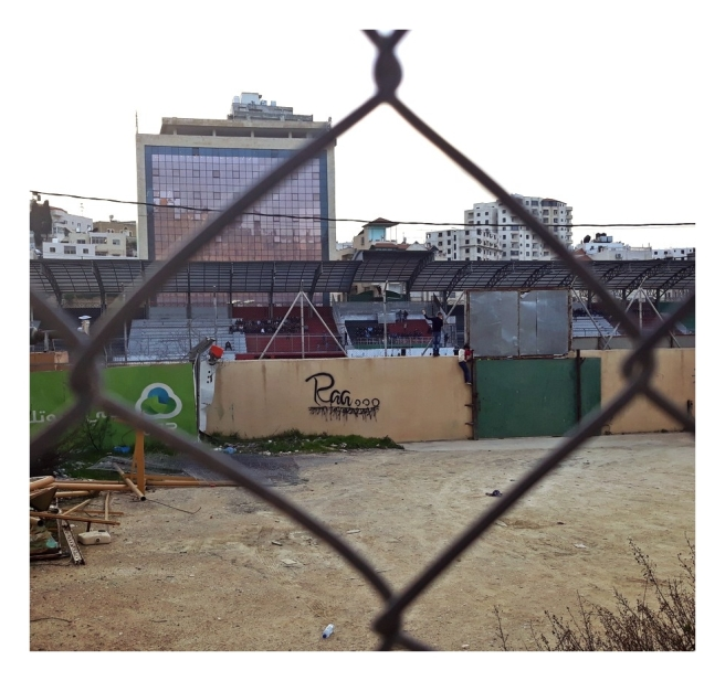 Football field in Hebron, children climbing over the fence